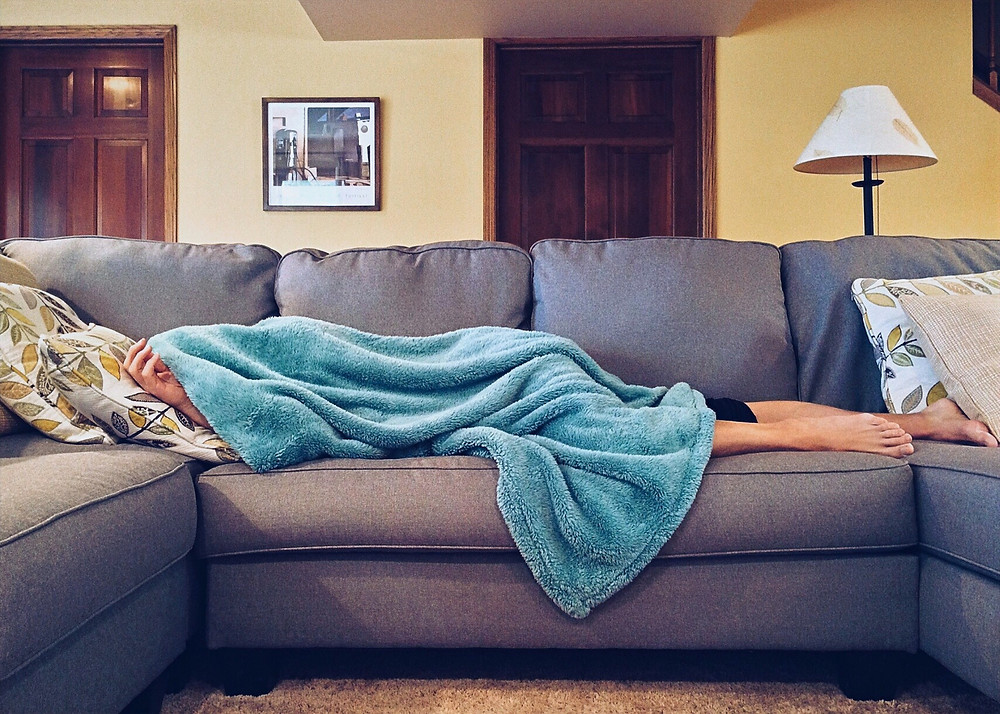 A person wrapped in a blanket lies on a couch with head resting on a boho pillow.