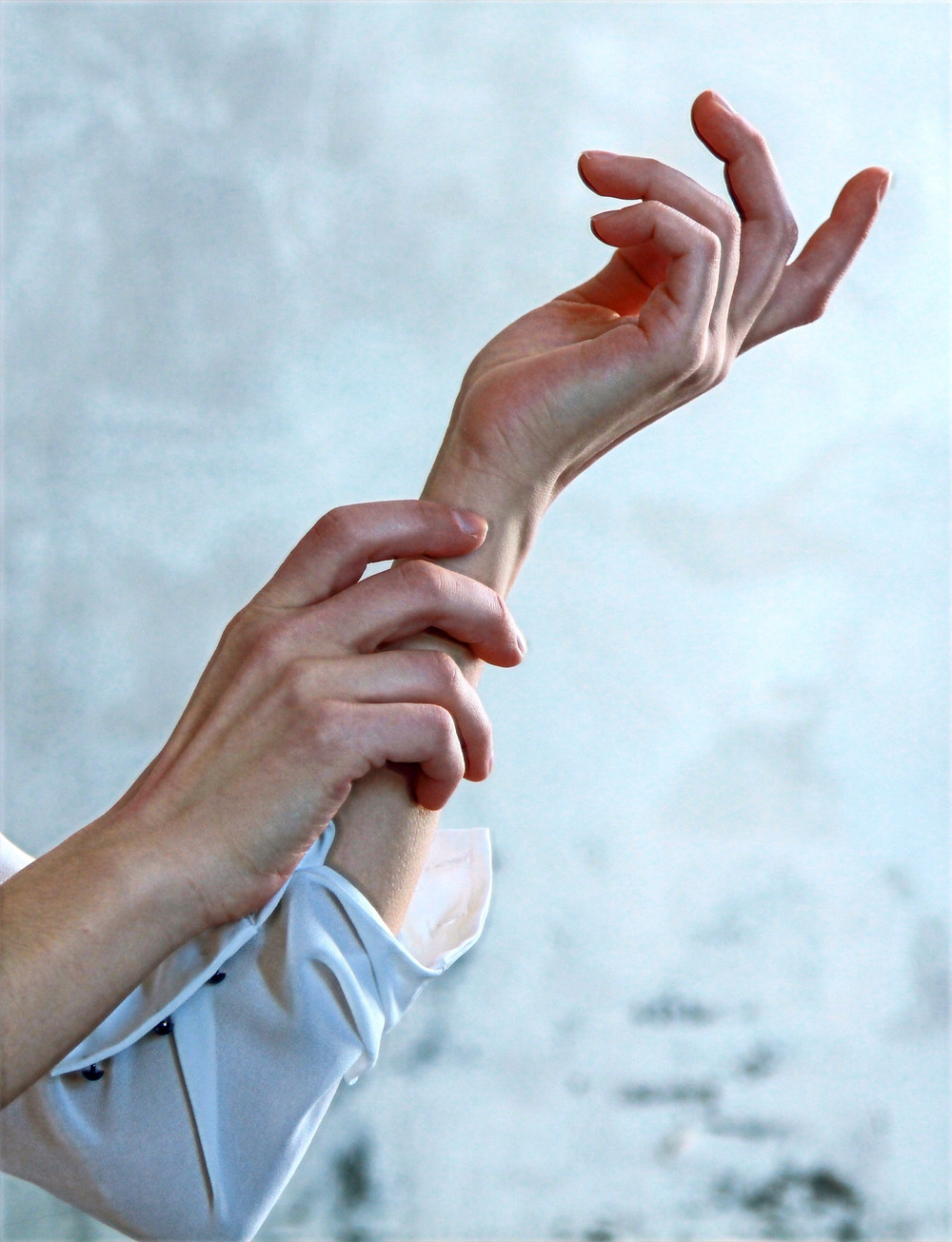 An image of a person conducting a compassionate body scan by gently feeling an area of the wrist.