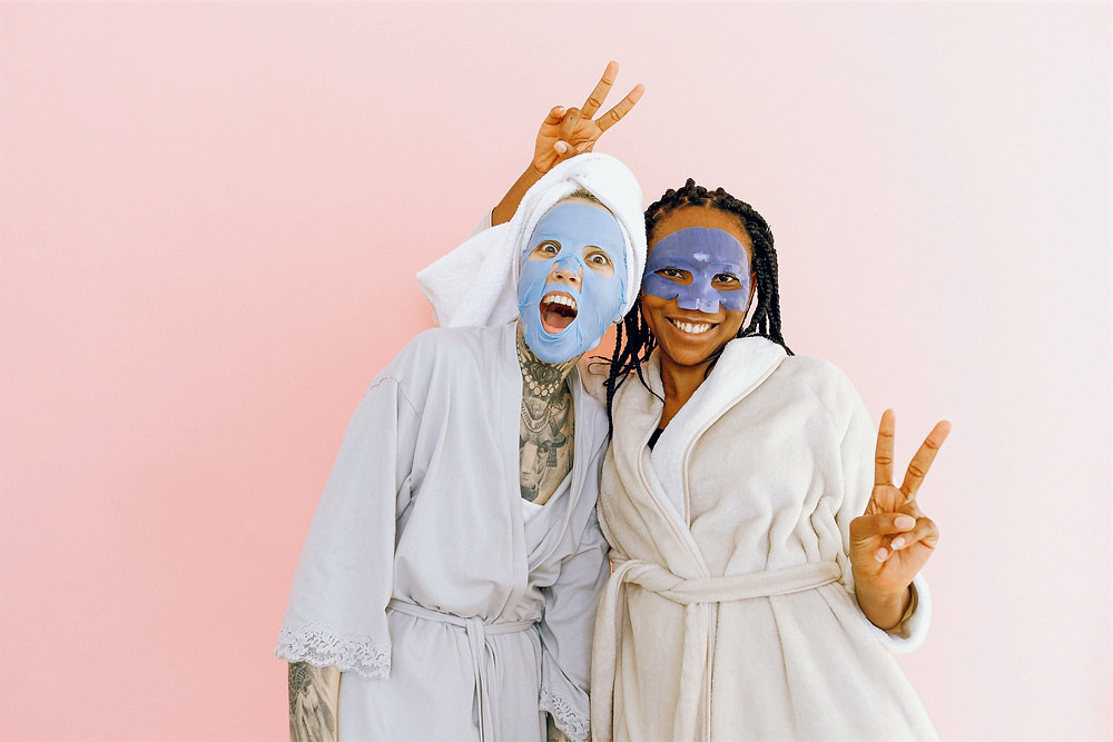 Two friends wearing hydrating sheet masks smile and pose for a photoshoot.