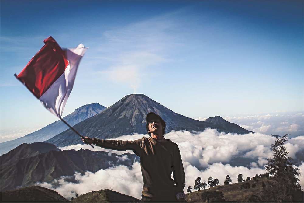A man wearing a hat and a sweater waves a red and white flat while gazing up at an open sky, as he stands in front of a range of mountains that are covered in a bed of clouds.