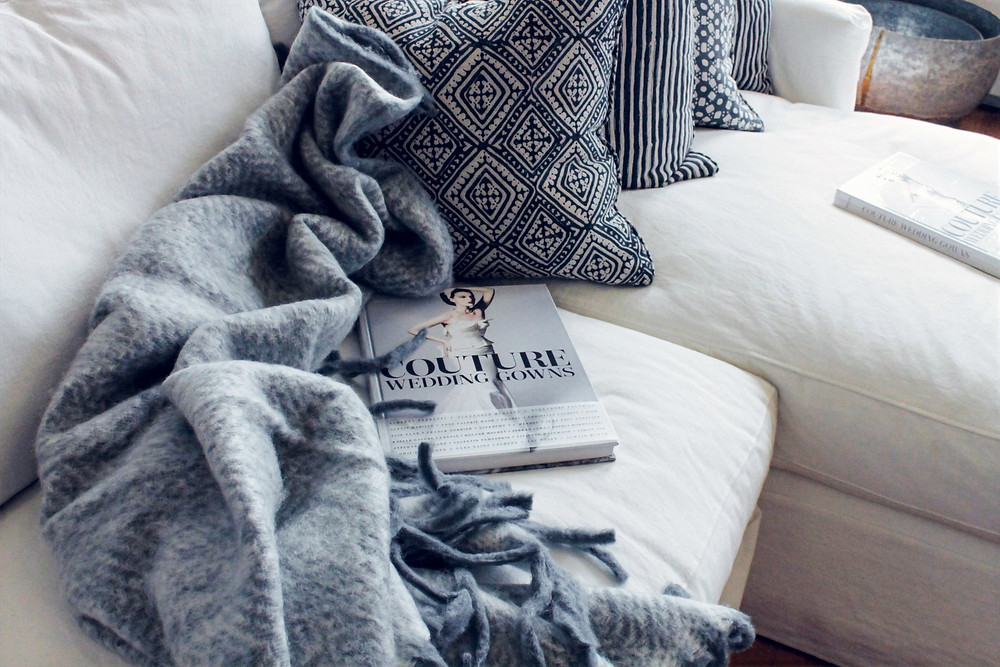 A boho chic style pillow, blanket, and couch are featured in a photograph, along with a copy of a Couture magazine.