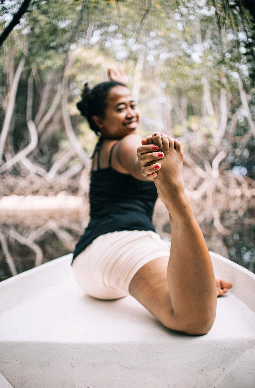 A woman holds a yoga pose while sporting an athleisure outfit and smiling into the camera during a photoshoot.