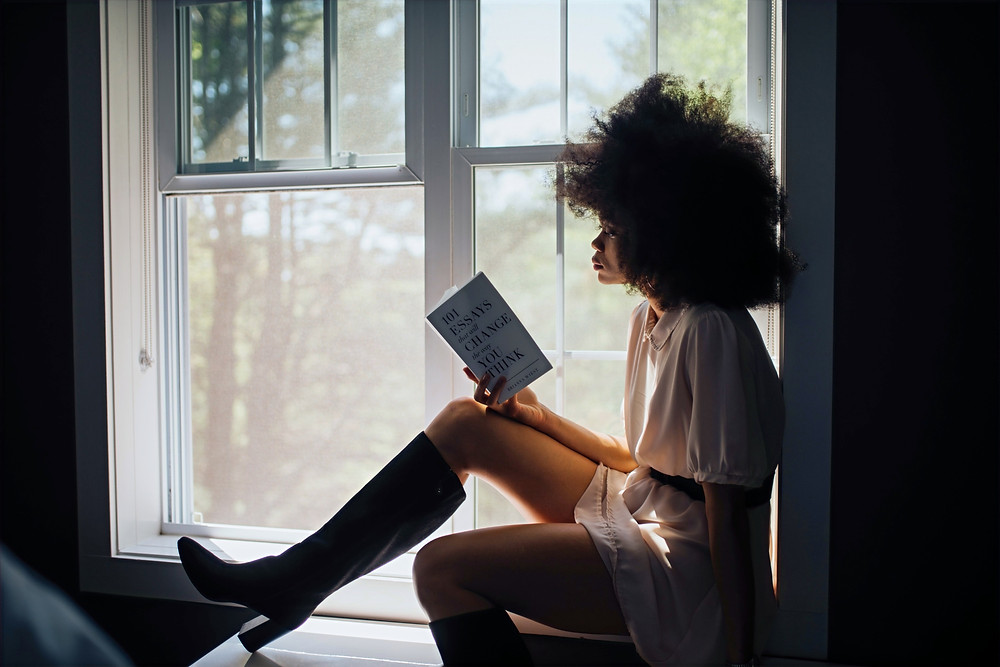 A woman sits on a window sill while reading a book about changing the way one thinks.