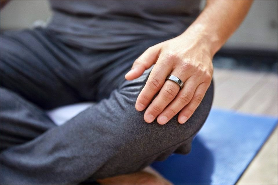 A person wearing an Oura Ring sits in lotus position while practicing yoga.