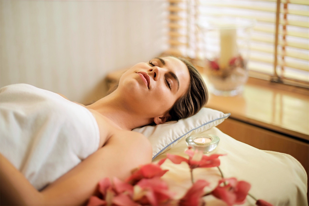 A woman lying down pleasantly on a bed after completing a skincare routine.