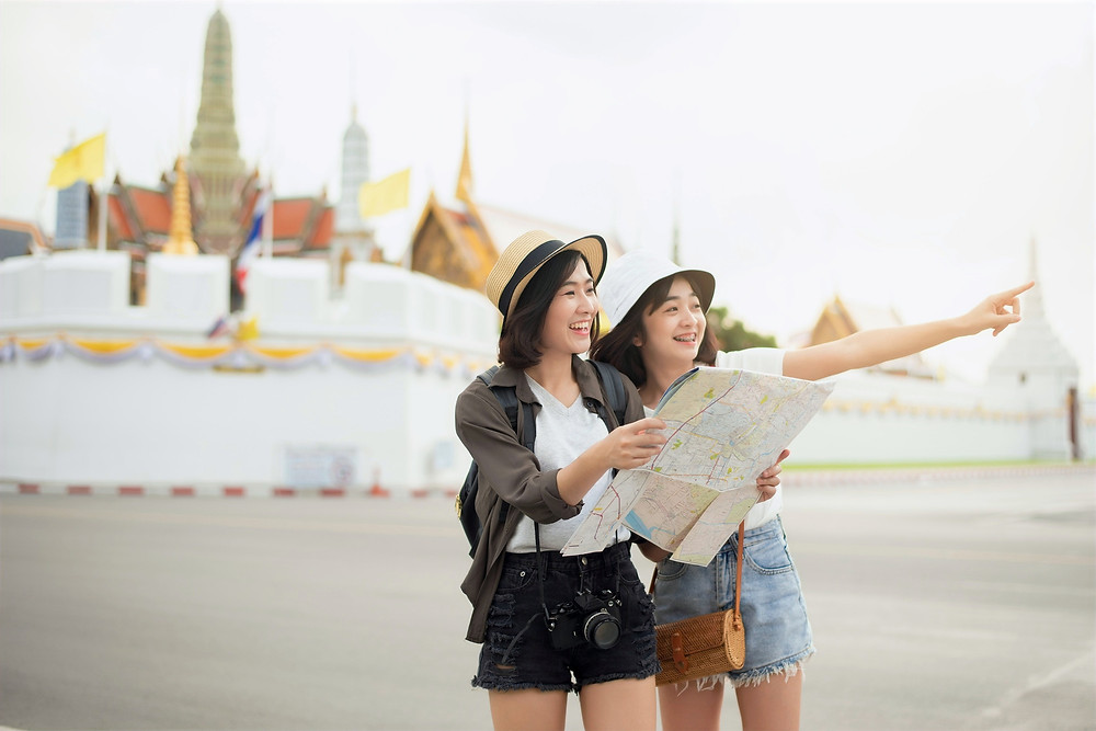 Two tourists smile and hold a map in front of a multi-colored temple surrounded by a white barrier.