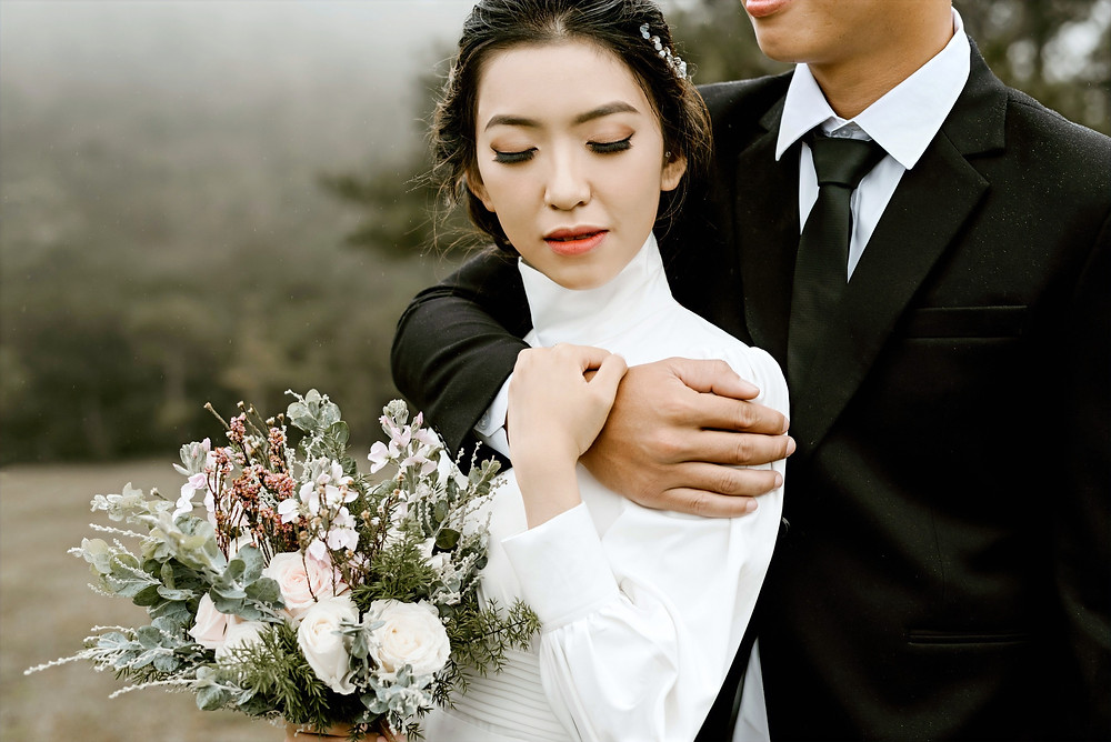 A newly wed bride holds a bouquet of flowers and she reaches for her husbands wrist as he wraps his arm around her chest in an embrace.
