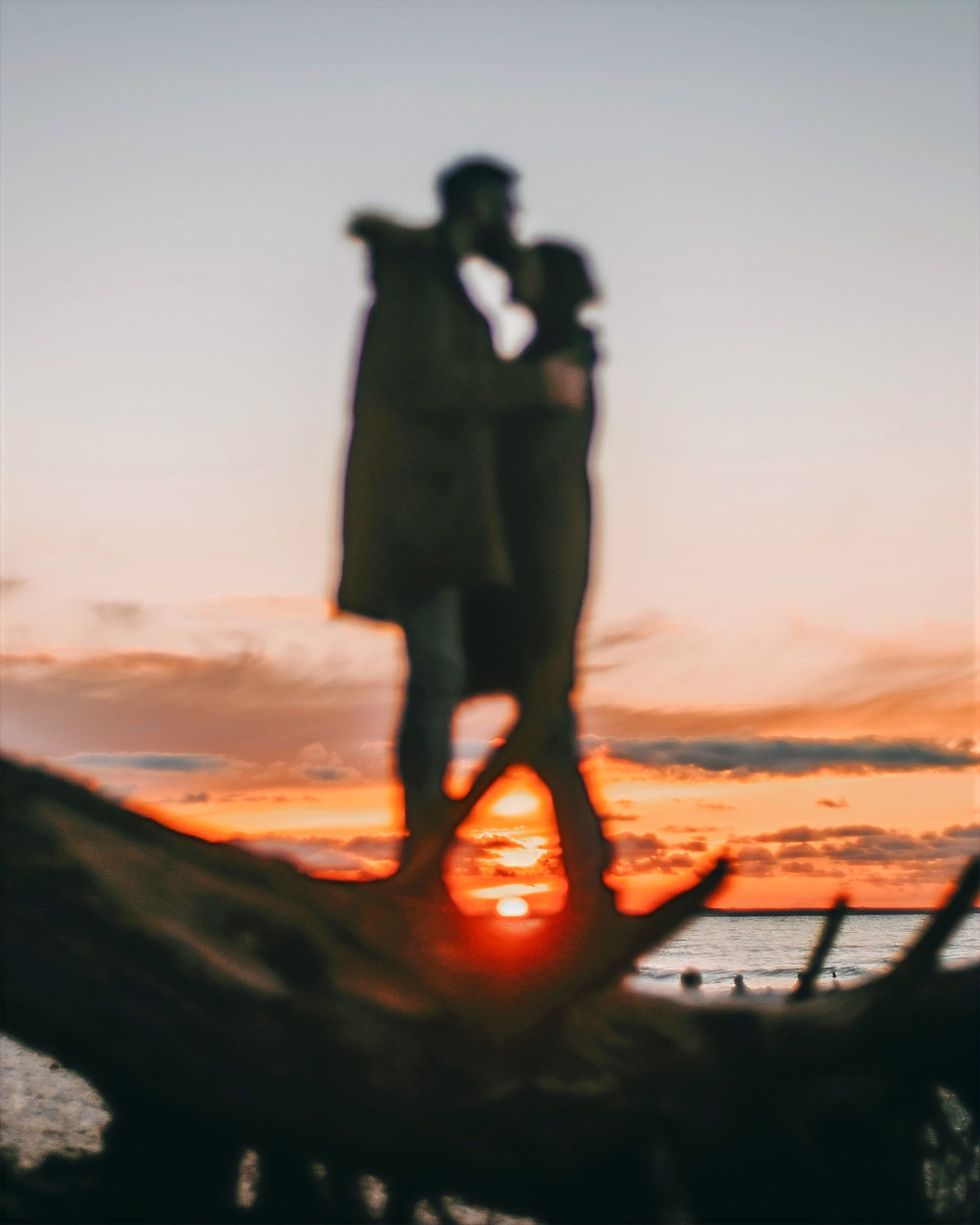 A couple embraces at sunset, displaying a sense of liminality and transition during a new phase of life.