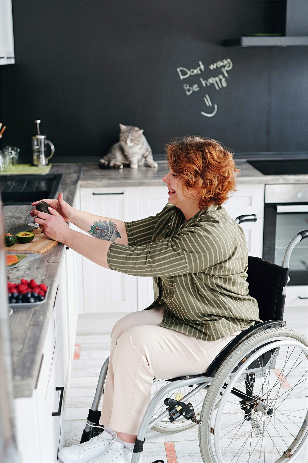 A person in a wheelchair picks up an avocado from a cutting board in a kitchen.