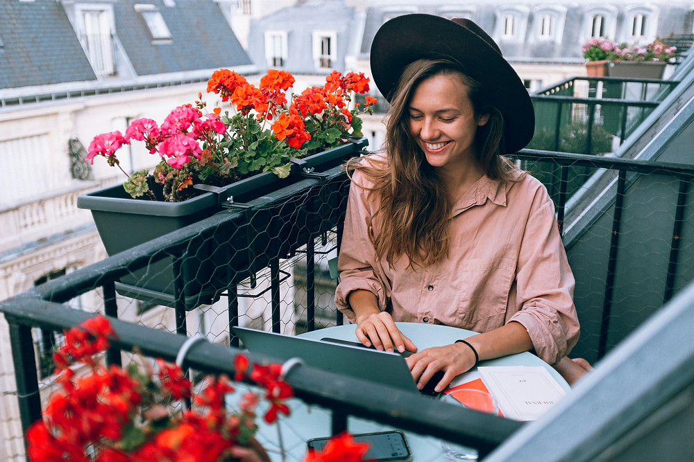A woman wearing a wide-brimmed hat and rustic blouse smiles while working on her computer, as she sits on a terrace balcony beside assorted red and pink flowers.