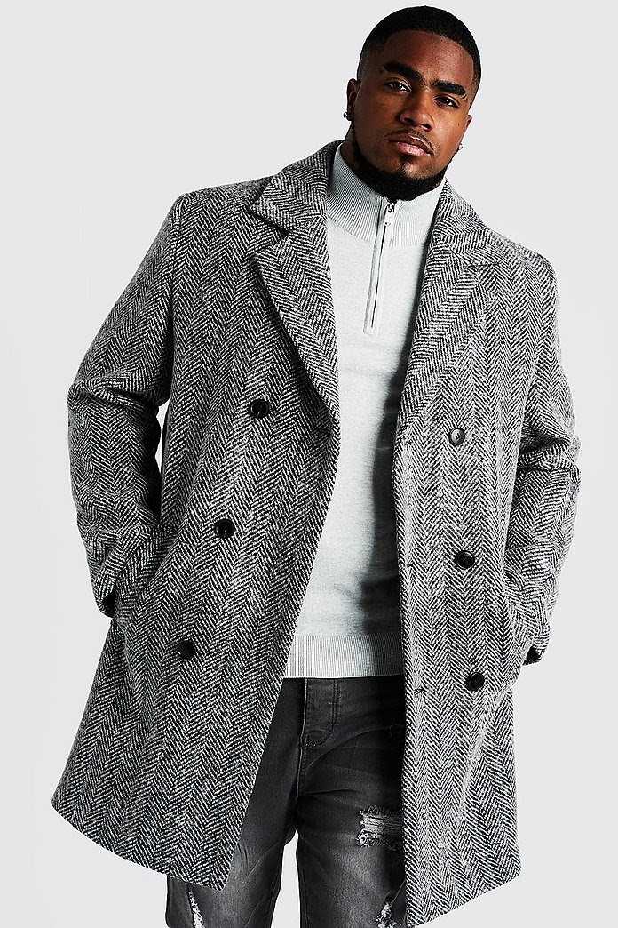 Man wears gray double-breasted wool blend overcoat to match his off-white sweater and gray jeans, a quality capsule piece