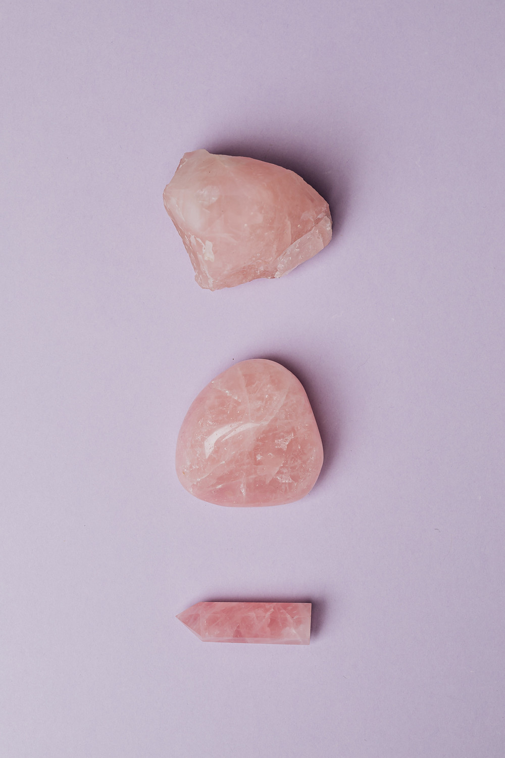 Three pink healing crystals are oriented in a vertical line and spaced evenly.