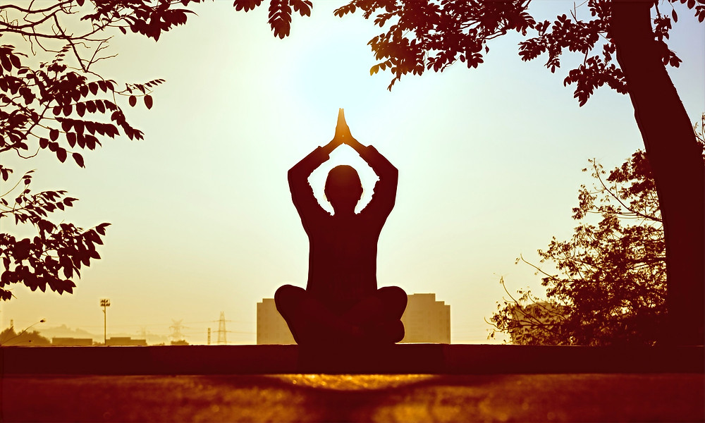 A person practices the art of meditation by sitting in a lotus position and raising their hands together at sunset.