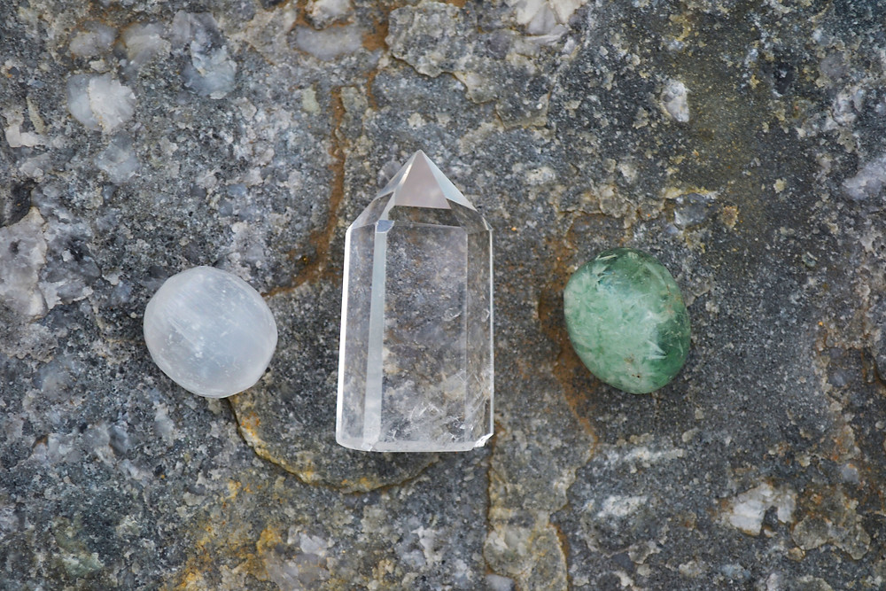 White, clear, and green healing crystals are placed in a symmetrical fashion, right to left.