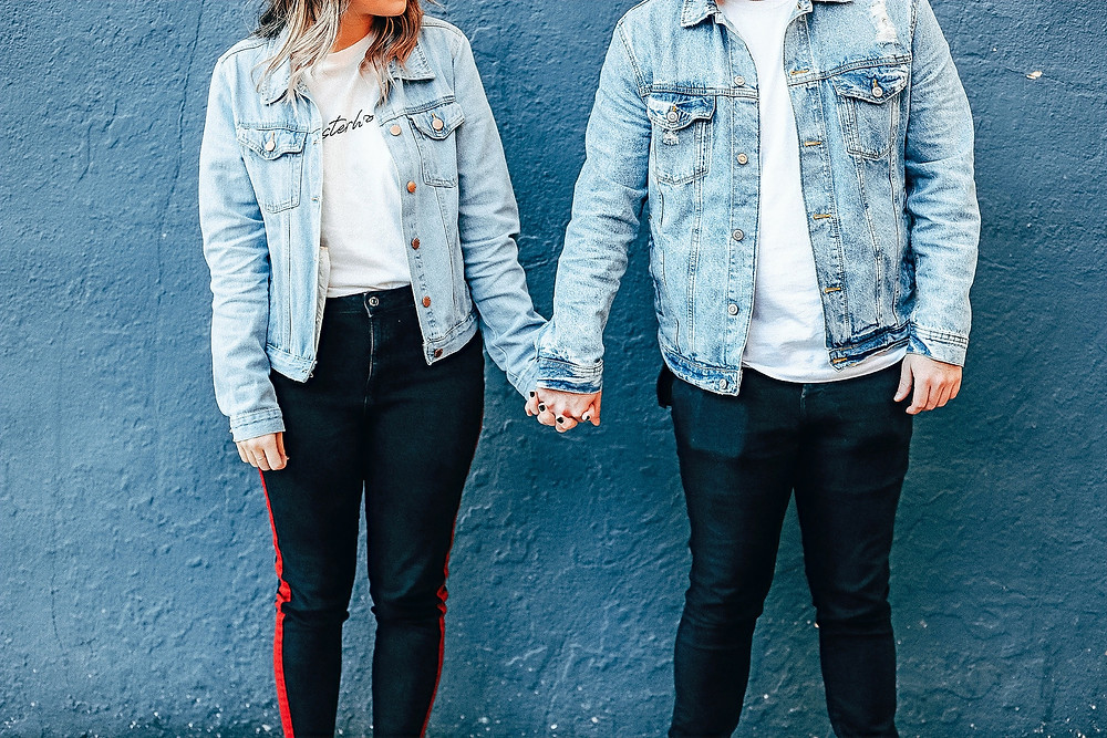 A couple wearing matching outfits comprised of white t-shirts, denim jackets, and black plants hold hands as they pose against a blue wall for a photoshoot.