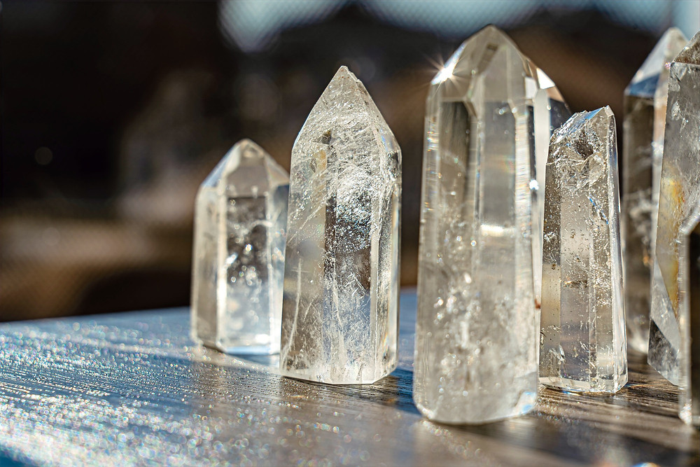 Fiver healing crystals are situated upright on an open wooden table.