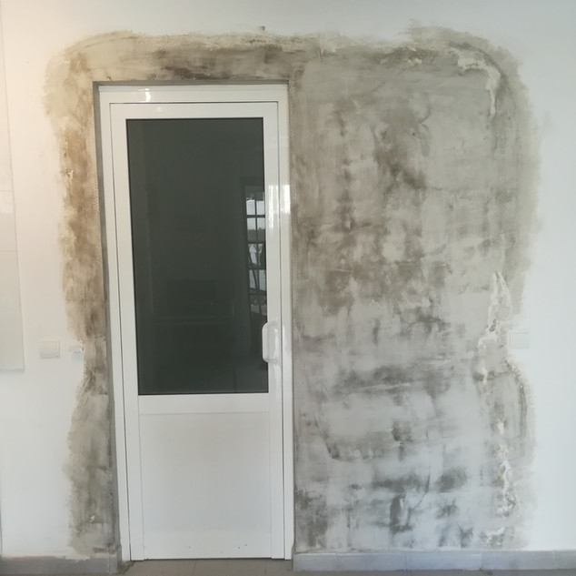 White aluminium door with smooth panel below and glazed panel above.