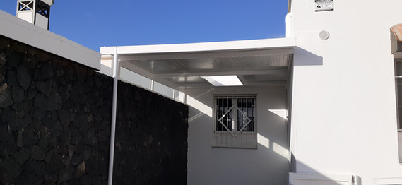 Carport with fixed glass on top of rock wall