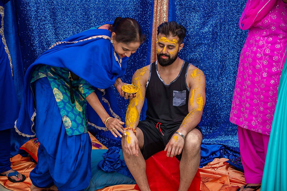 auntie in blue sari taking her turn to rub more paste onto sitting grooms hand with turmeric paste