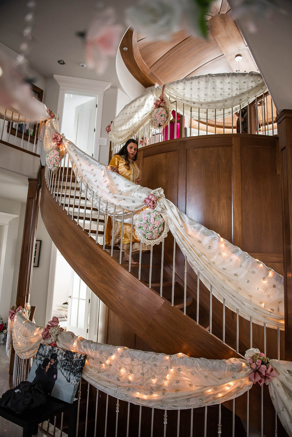 bridesmaid in yellow saree walking down brown spiral staircase decorated with pink bows and large white silver spotted ribbon