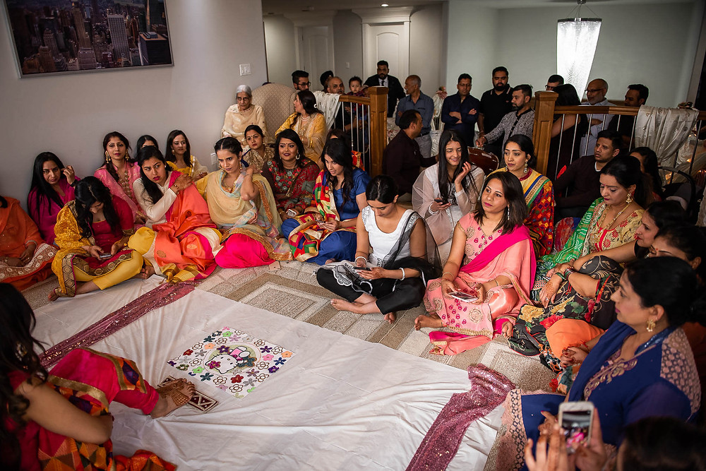 women sitting around the bride at maiyan ceremony with hello kitty rangoli on the floor