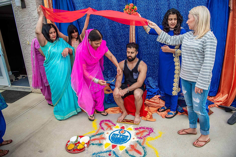 groom sitting on red stool in behind edmonton oilers rangoli with four women holding red scarf above his head white mother in pink sari puts on a silver bracelet for him