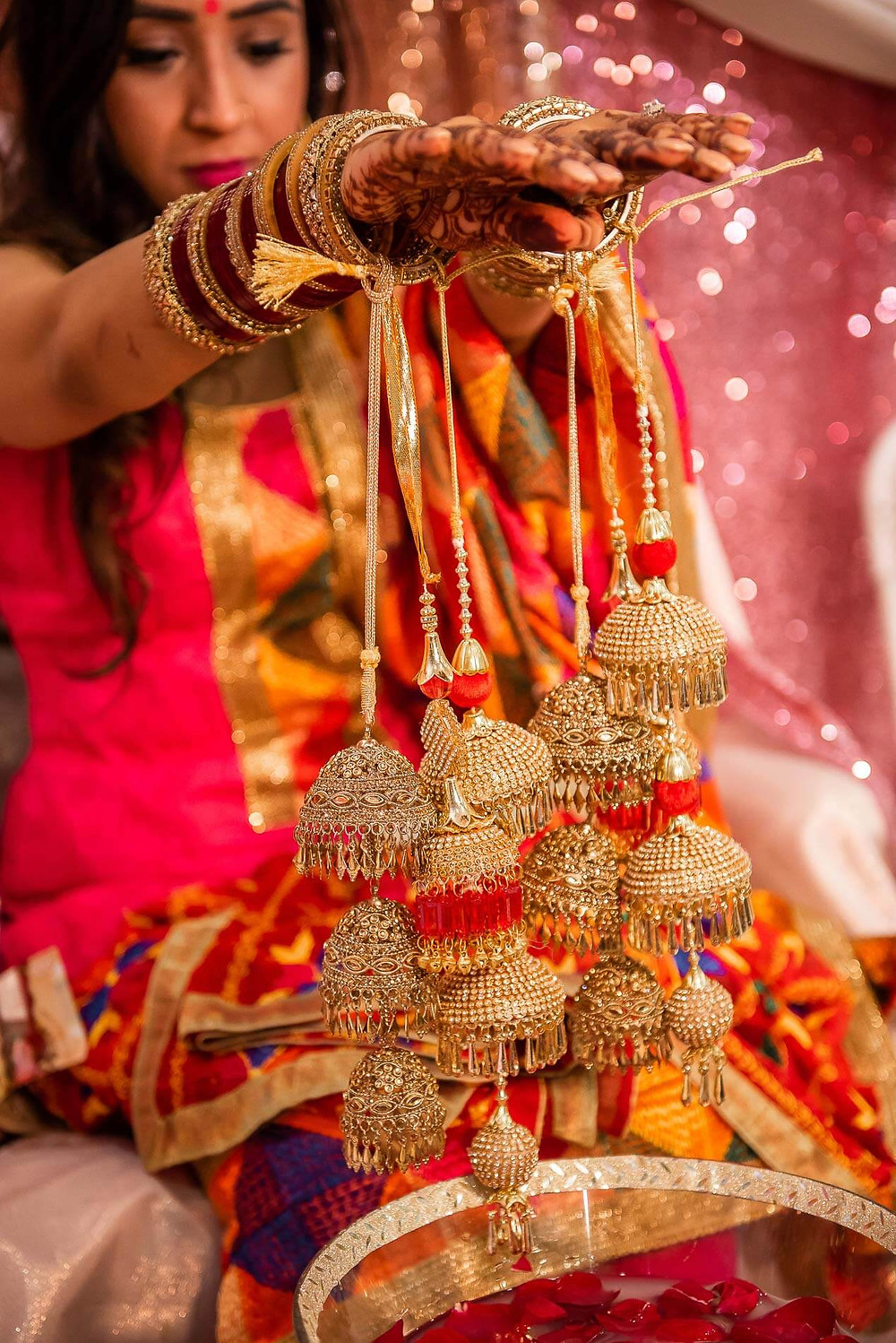 Close up of bride holding out her arms in front of her dangling gold decorations tied to her red bangles