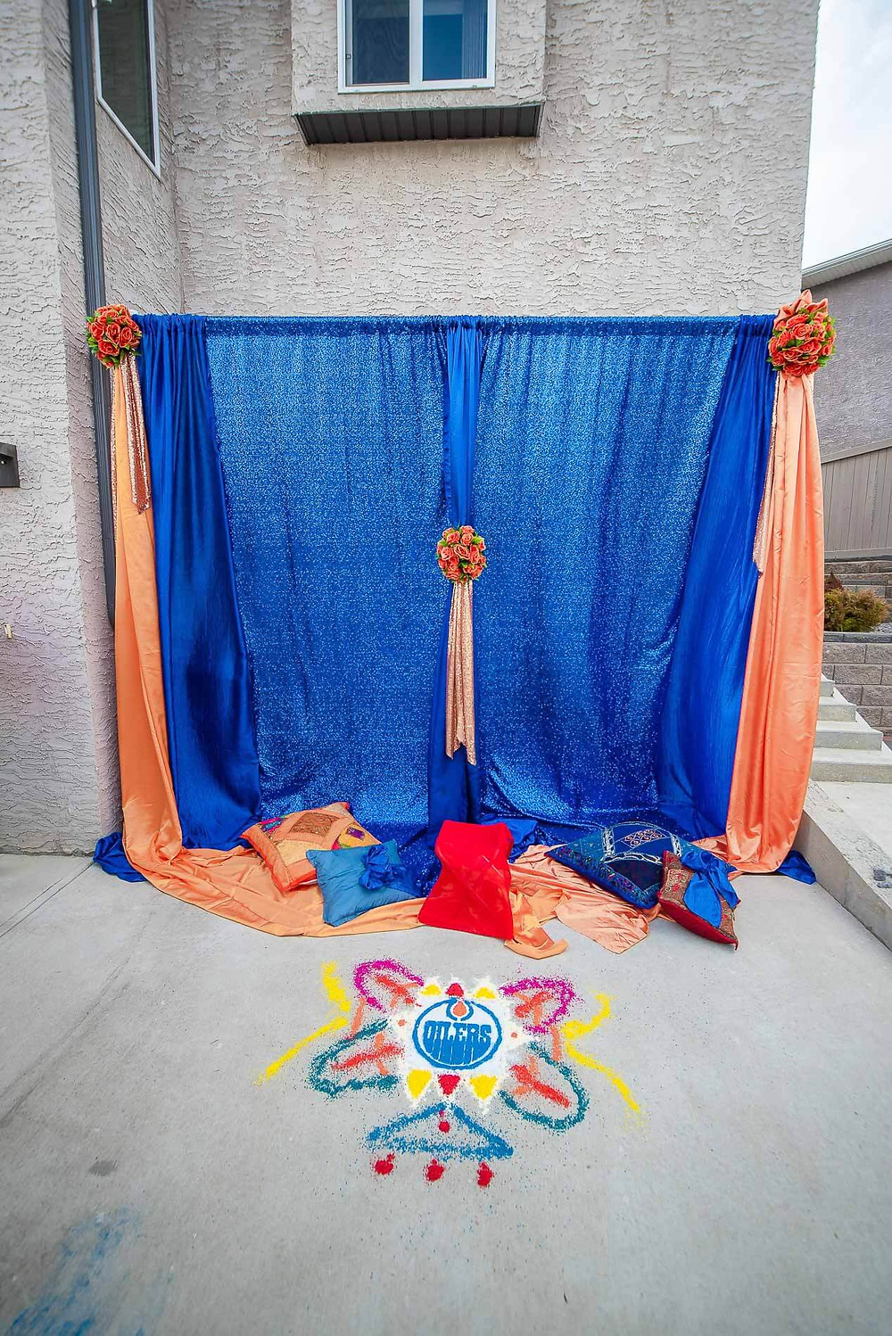 full set up for grooms Maiyan ceremony with royal blue curtains and peach trim with bouquet of flowers in the middle and edmonton oilers rangoli on the cement floor