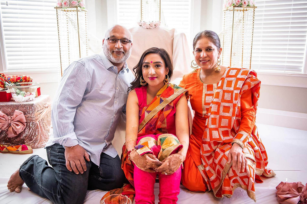 bride to be in red saree sitting with mom and dad for a family portrait