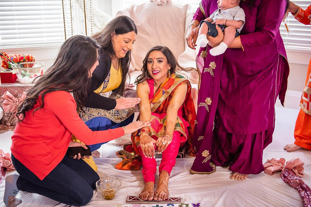 two aunties rubbing turmeric paste on bride's arm wearing red sleeveless saree