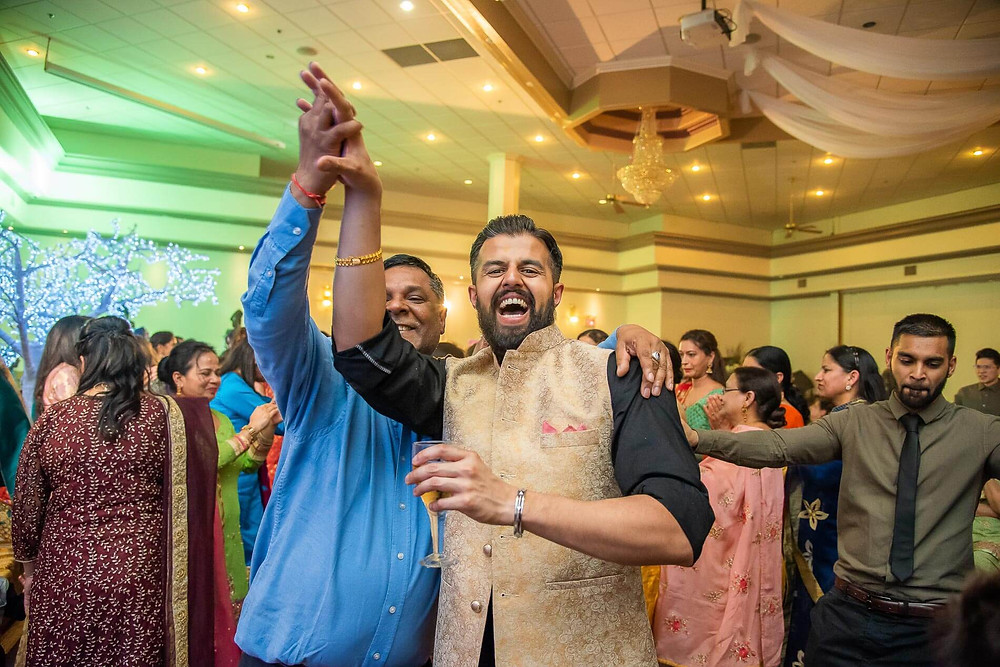 groom in gold with big smile dancing in a crowd hands held high with father in blue shirt