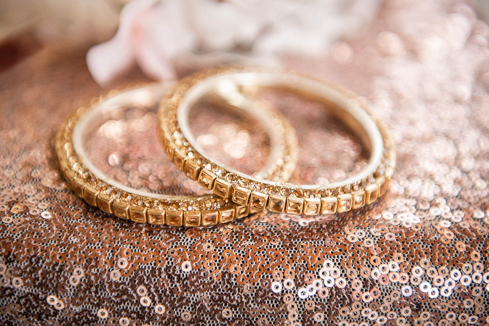 Close up of two gold wedding bands encrusted with diamonds on rose gold carpet