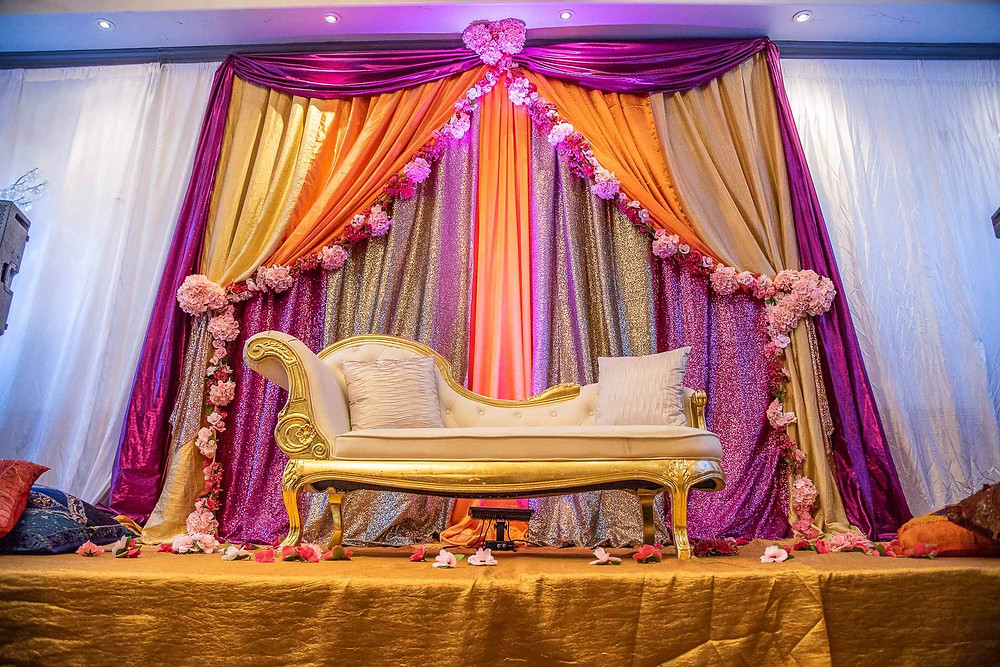 Gold couples chair in front of a purple gold and orange drapes with real rose trim