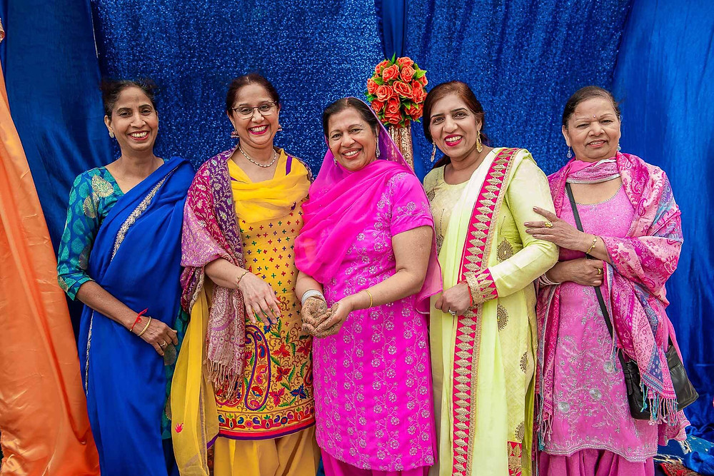 5 women in different coloured sari's smiling for a photo with sparkling blue background