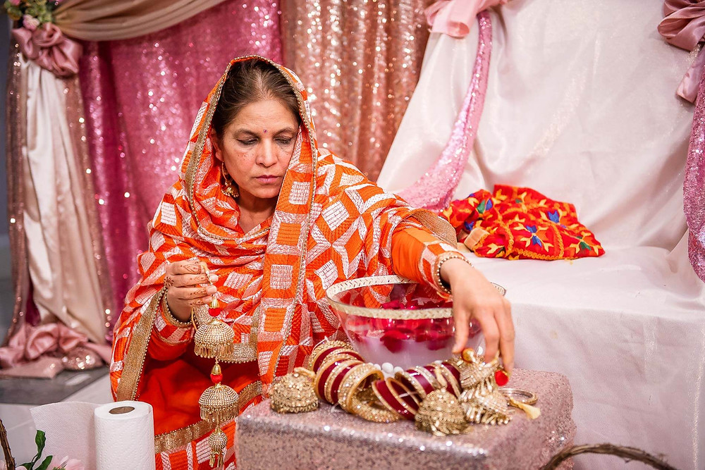 auntie setting up red and gold bangles or chooriyan on a stool in front of brides chair