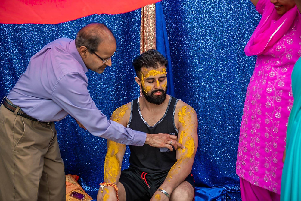 father rubbing yellow turmeric paste onto groom's arm