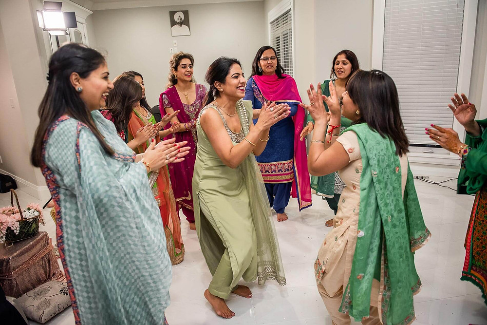 circle of aunties in sarees dancing and clapping hands at mehndi ceremony