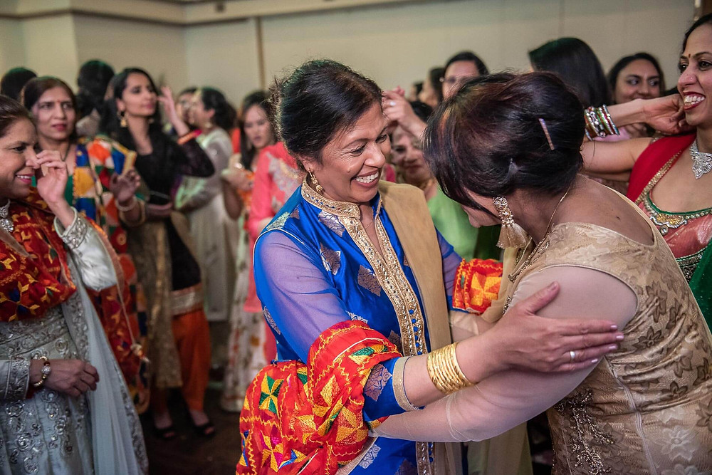 mom in blue saree embracing an auntie in rose gold saree