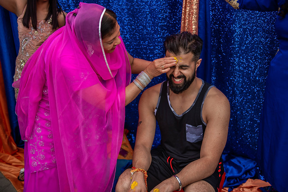 mother in pink sari rubbing turmeric paste onto the forehead of smiling and sitting groom