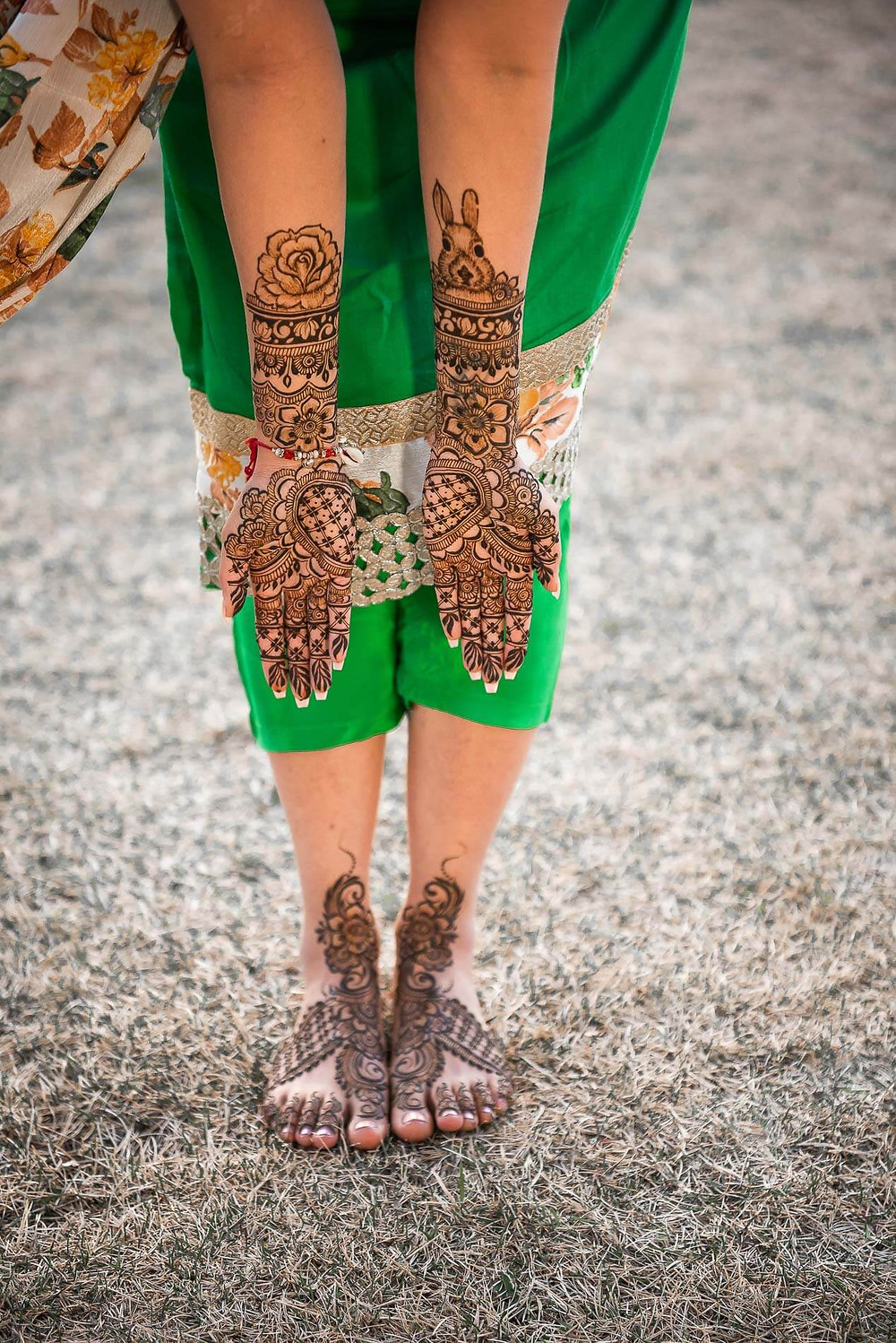 woman in green dress leaning over showing henna design on the backside of her hands and henna design on feet