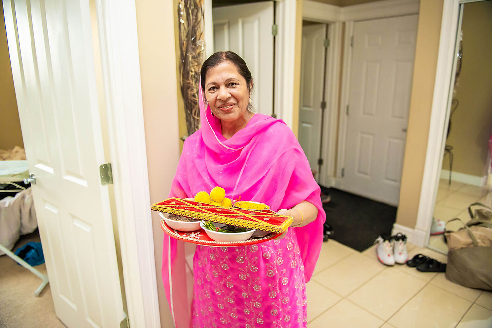 portrait of grooms mother in pink sari holding tray of traditional treats for ceremony