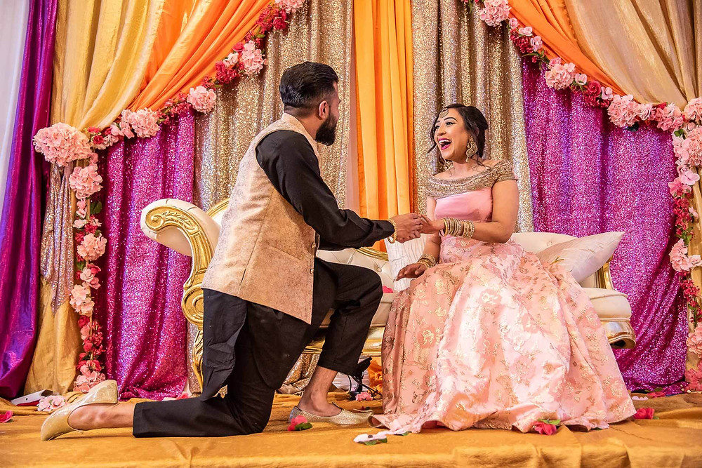 groom_on_one_knee_proposing_to_sitting_bride_in_pink_gold_dress_with_orange_sparkly_pink_curtains_in_background