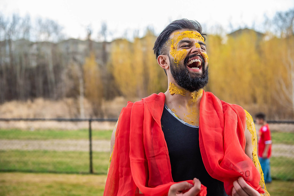 portrait photography of groom with turmeric on his face and red scarf laughing in the air