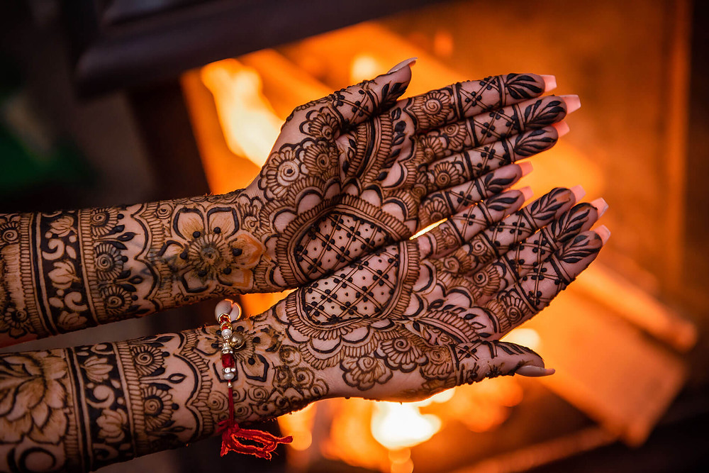 close up holding out both hands with henna design from arms to hands in front of an outdoor fire