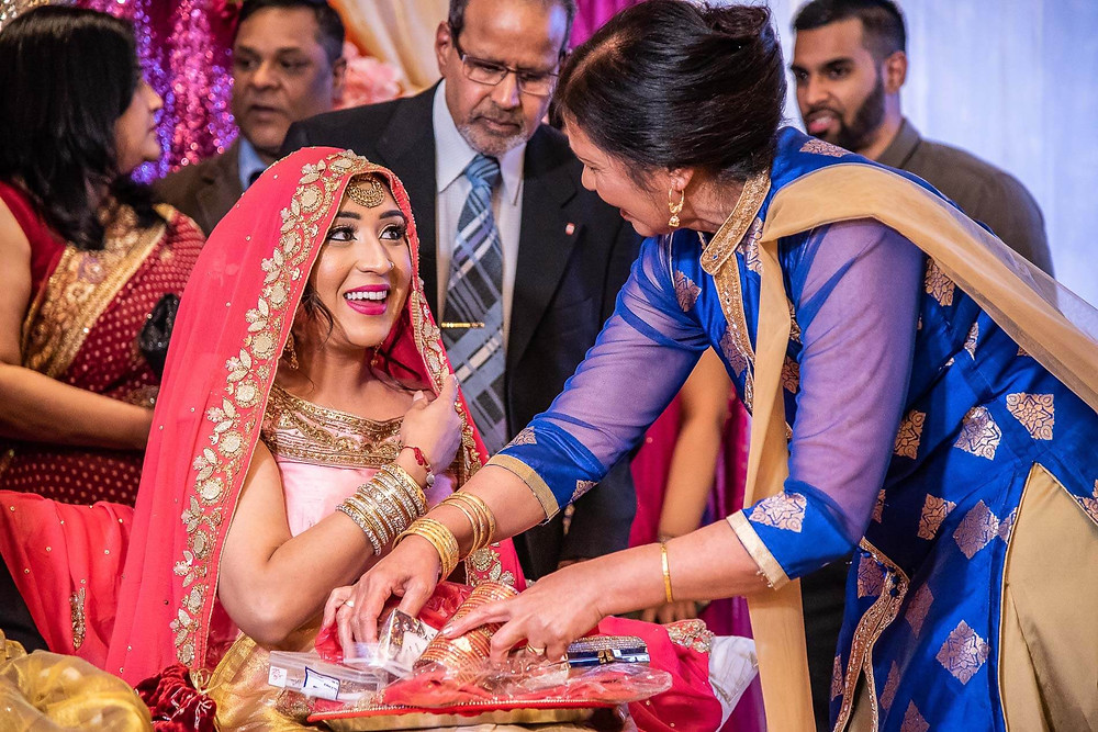 mother in blue saree putting on bracelets and bangles on sitting bride in red chunni