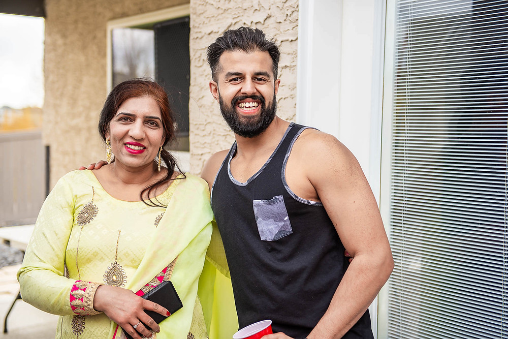 portrait photo of groom in black sleeveless shirt and auntie in yellow sari