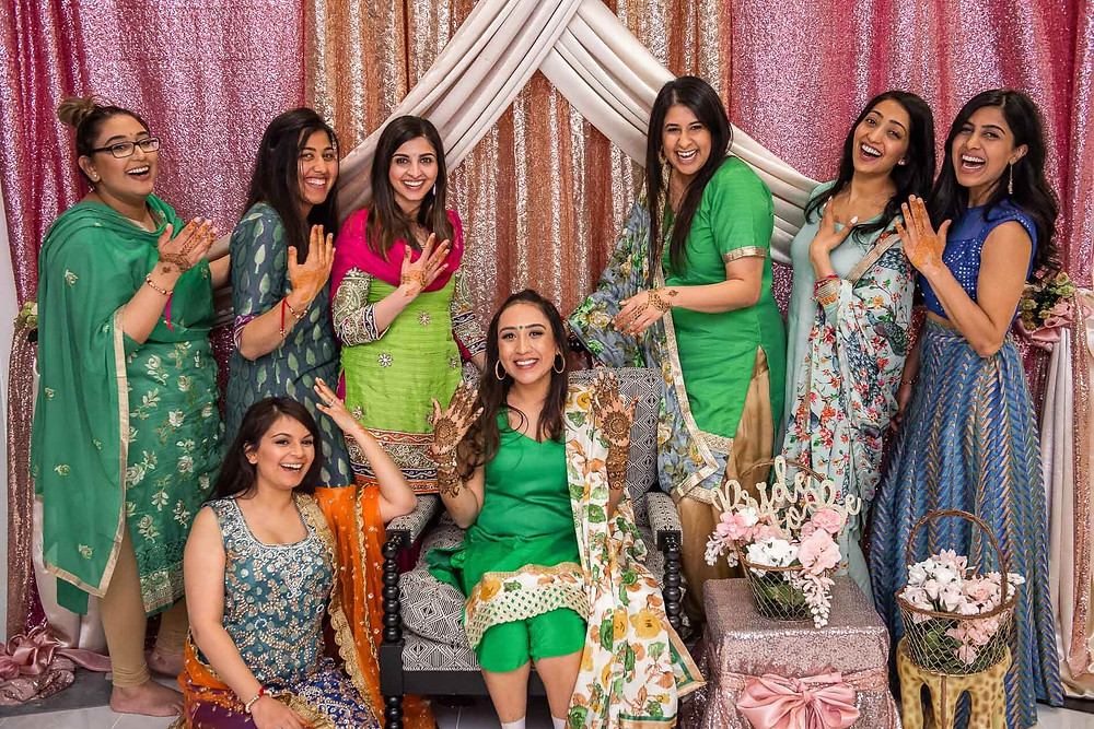 women posing in saree posing showing their henna designs on hands with sparkly pink and orange curtains in the background