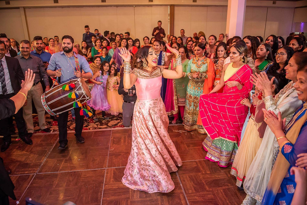 Bride in pink saree dancing in the middle of a crowd with hands raised