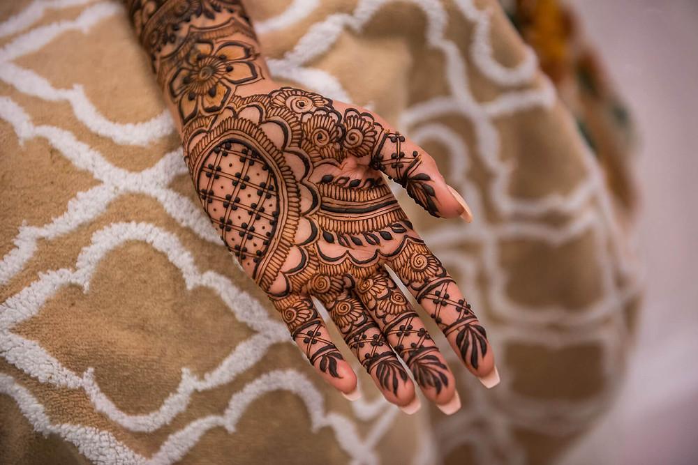 henna_design_inside_palms_on_light_brown_blanket