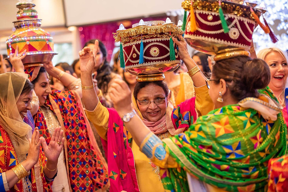 women in colourful sarees dancing together with their hands up